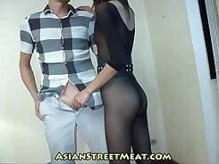 Alluring brunette in black stockings is walking down the street